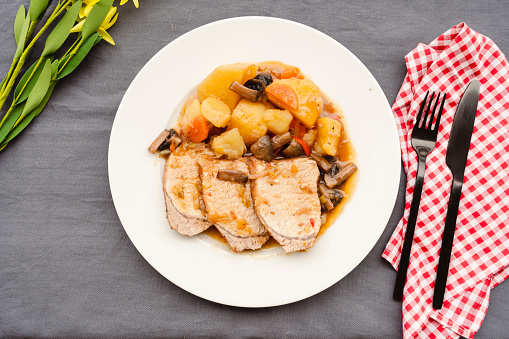 Homemade a Pork Loin with potatoes and mushrooms in sauce to the saucepan of long or slow cooking. Homemade food concept, healthy and natural food, slow cooking. Overhead view.