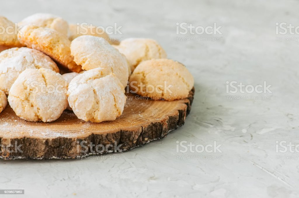 Homemade amaretti cookies on a wooden board on a white stone backdrop. stock photo