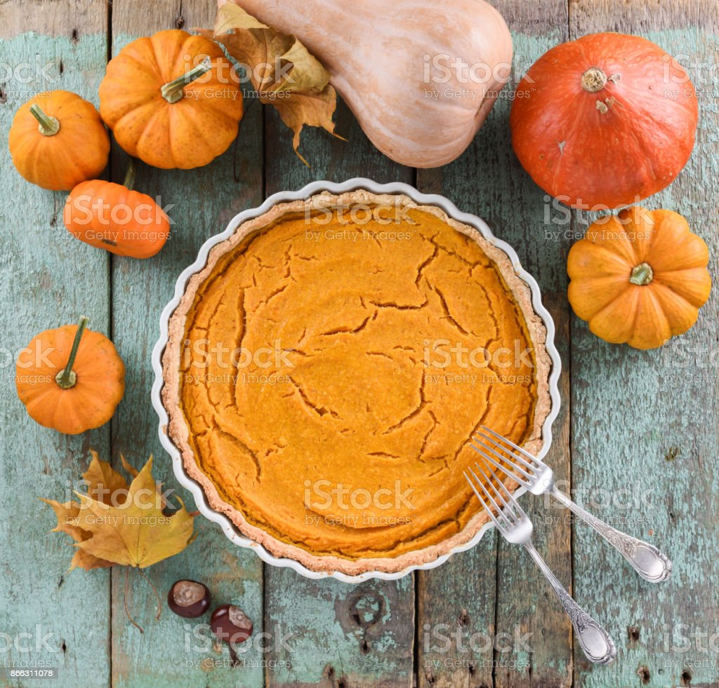 Homemade American pumpkin pie in white ceramic dish surrounded with small pumpkins, marple leaves and chestnuts on blue wooden background stock photo