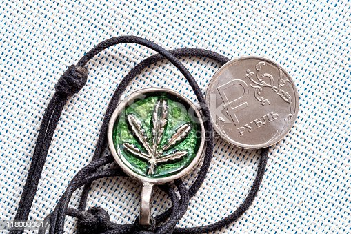 istock homemade amulet and coin on fabric background 1180000317
