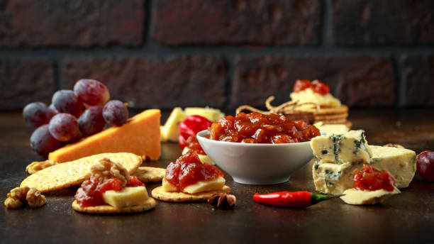 Homemade apple and chilli chutney with cheese, snack, nuts, fruits stock photo