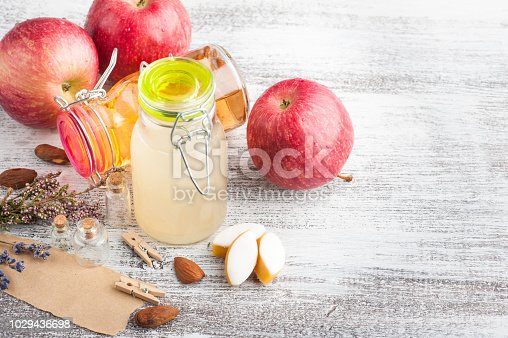 Homemade apple cider and fresh apples on wooden table