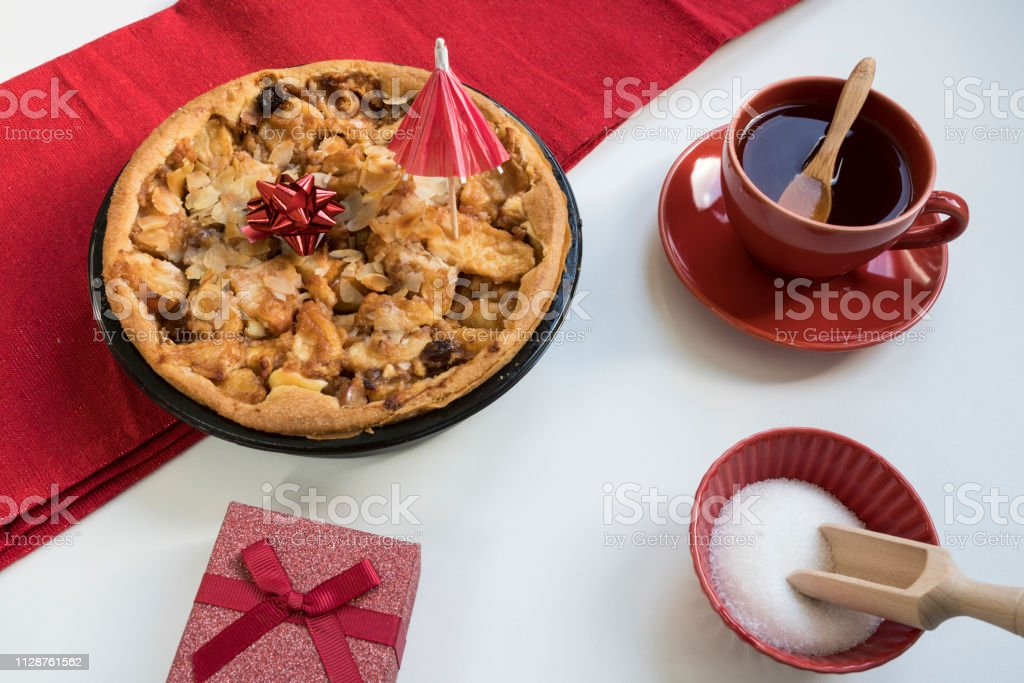 party scene with Dutch apple pie, hot beverage and gift box