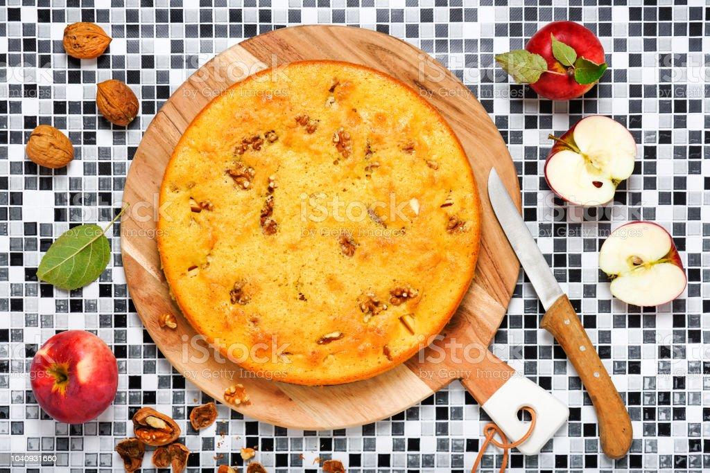 Torta de maçã caseira com maçãs frescas e nozes na tábua de madeira. - foto de acervo