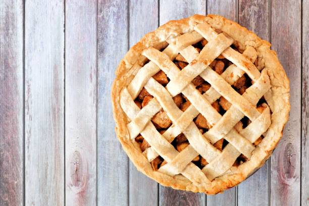 Homemade apple pie with lattice pastry over aged wood stock photo