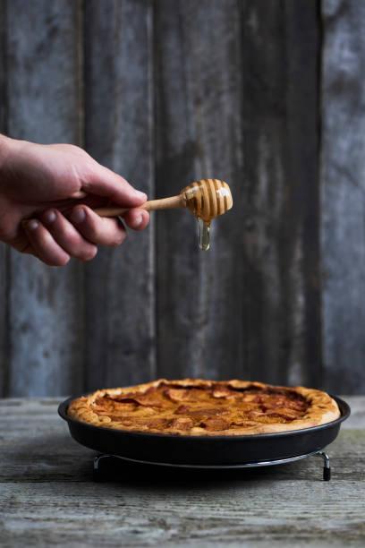 hausgemachte quitte apfelkuchen mit hölzernen honig dipper auf rustikalen hintergrund. ansicht von oben - quittenkuchen stock-fotos und bilder