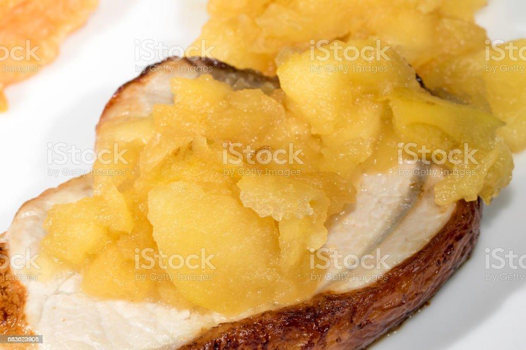 Homemade apple sauce on a pork loin steak stock photo