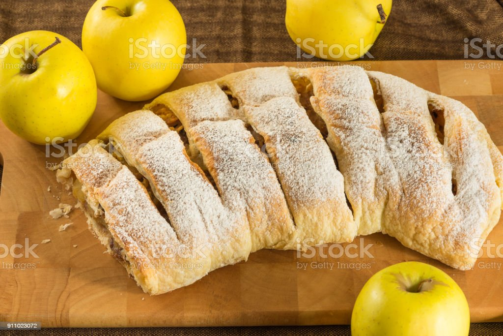 Homemade apple strudel (apples pie) with puff pastry, cinnamon and raisin stock photo