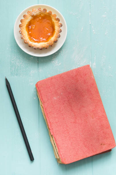 Homemade apricot cake on turquoise wooden background, with a pencil and vintage book. - foto stock