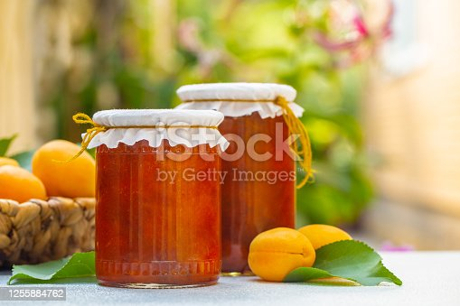 Homemade apricot jam. In the garden. Copy space.