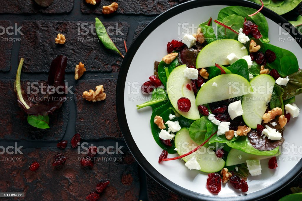 Homemade Autumn Apple Cranberry Salad with walnut, feta cheese and vegetables stock photo