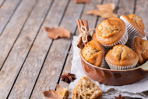 Comfort food. Homemade autumn cakes or muffins with nuts and spices on a wooden table. Autumn or fall baked pastry. Copy space background