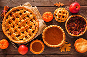 Homemade autumn pies. Apple, pumpkin and pecan. Top view table scene on a rustic wood background.