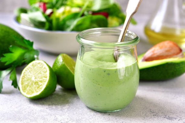 Homemade avocado yogurt dressing in a vintage glass jar Homemade avocado yogurt dressing in a vintage glass jar with ingredients for making on a light slate, stone or concrete background. savory sauce stock pictures, royalty-free photos & images