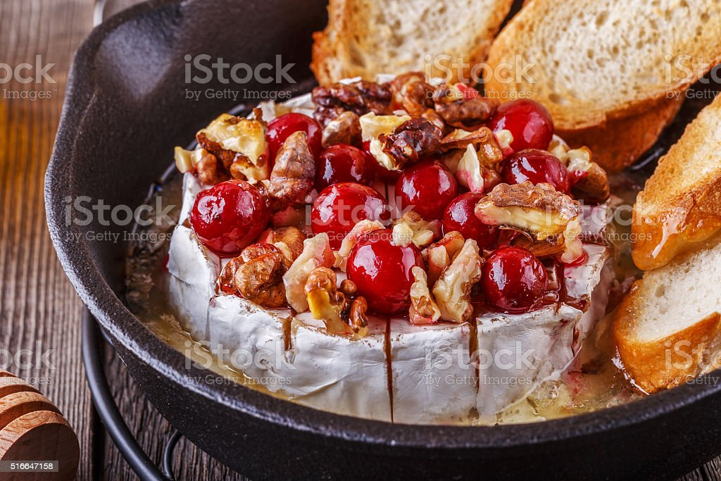 Homemade baked brie with honey, cranberry and walnut. stock photo