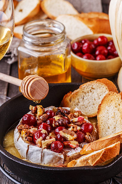 homemade baked brie with honey, cranberry and walnut. - baked brie stock photos and pictures