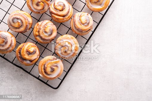 Homemade baked cinnamon rolls on cooling on cooling rack