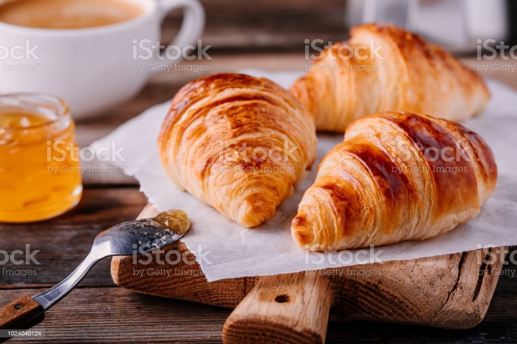 Homemade baked croissants with jam and coffee on wooden rustic background stock photo