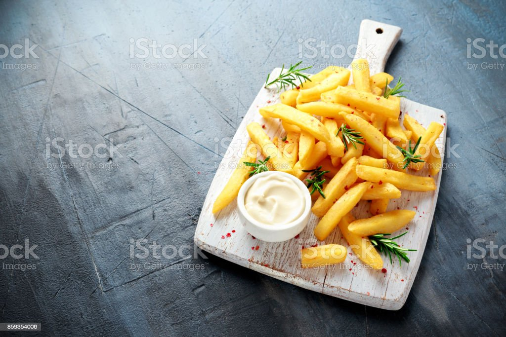 Homemade Baked Potato Fries with Mayonnaise and rosemary on white wooden board - fotografia de stock
