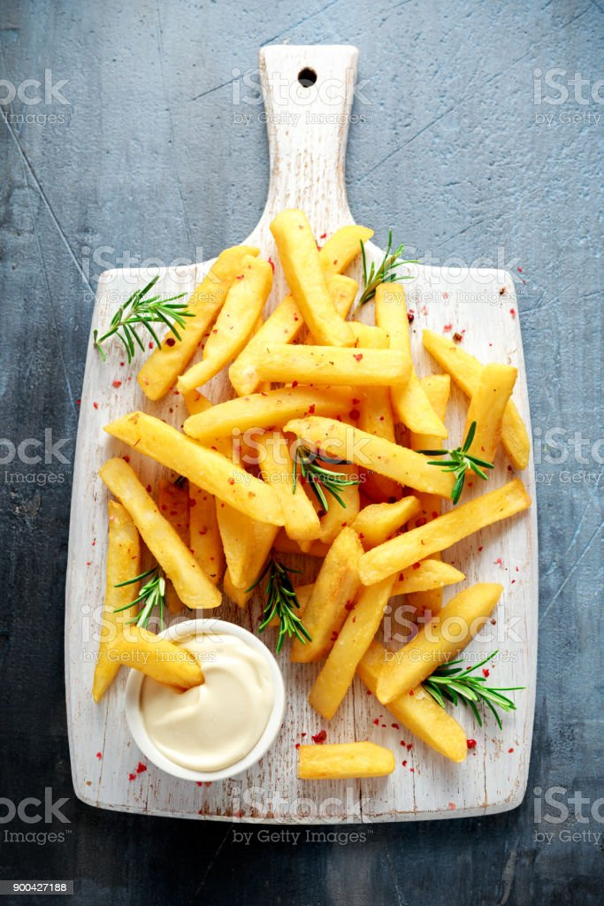 Homemade Baked Potato Fries with Mayonnaise and rosemary on white wooden board stock photo