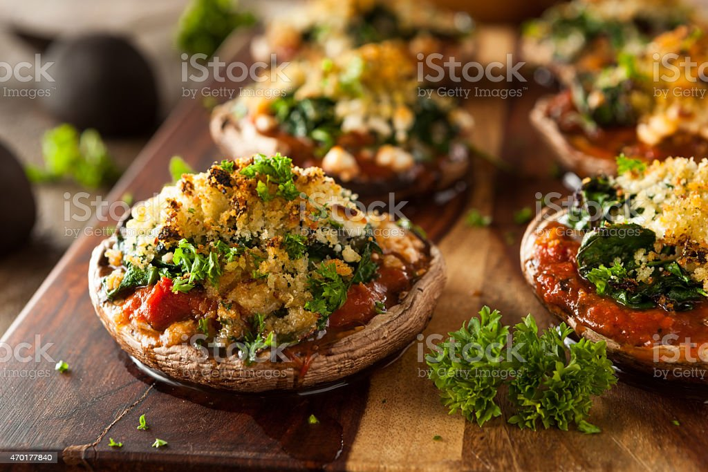 Homemade Baked Stuffed Portobello Mushrooms on wood board stock photo