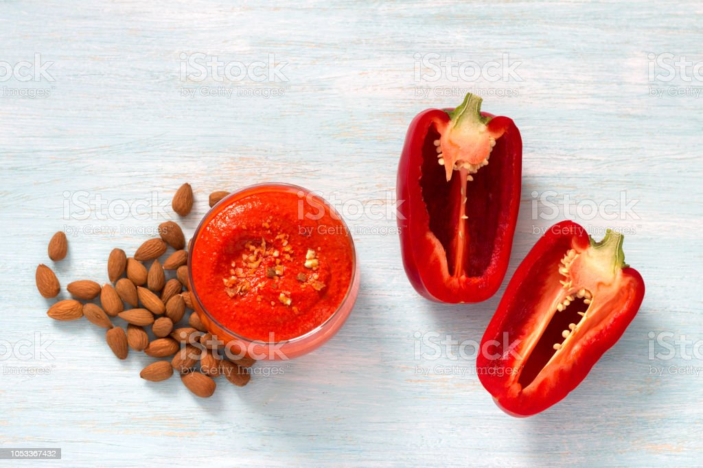 Homemade baked sweet bell pepper dip with almonds on a light blue background stock photo
