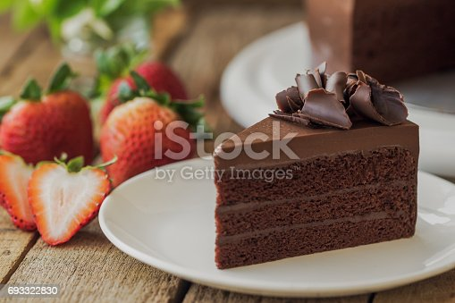 istock Homemade bakery: chocolate fudge cake decorated with chocolate curl. Triangle slice piece of chocolate cake on rustic wood table for cafe,meeting, coffee break or tea time and birthday party. 693322830