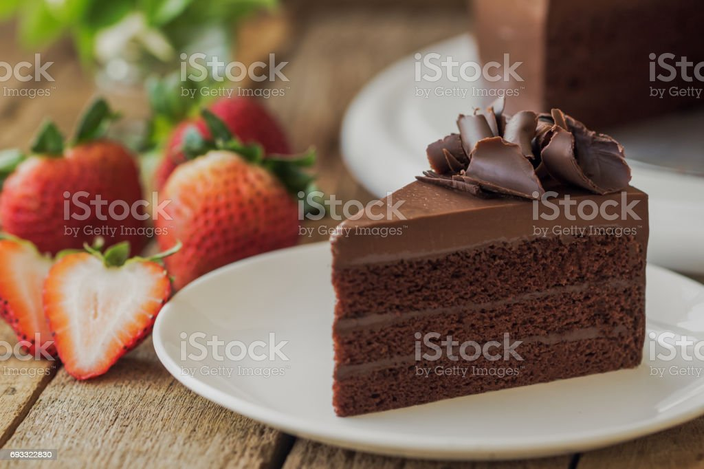 Homemade bakery: chocolate fudge cake decorated with chocolate curl. Triangle slice piece of chocolate cake on rustic wood table for cafe,meeting, coffee break or tea time and birthday party. stock photo