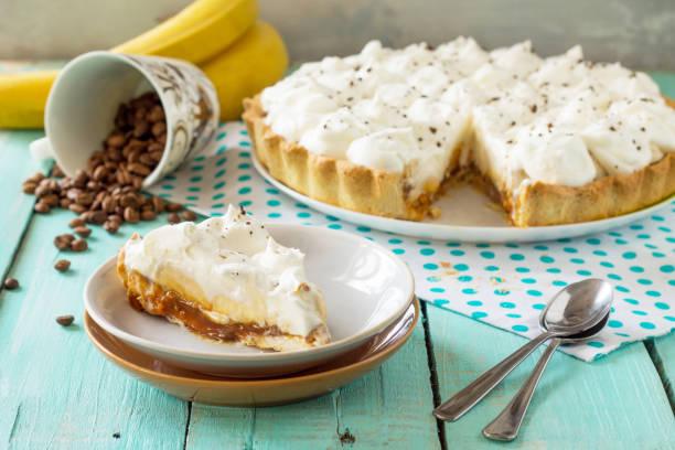 """homemade backen. """"banofi"""" kuchen mit karamell und banane auf rustikalen holztisch. - gebackene banane stock-fotos und bilder"""