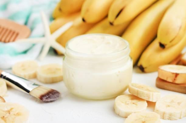hausgemachte banane hautpflege behandlung schönheitsmaske. glas mit aromatischen körper butter, frische reife gelbe früchte - makeup selbst gemacht stock-fotos und bilder