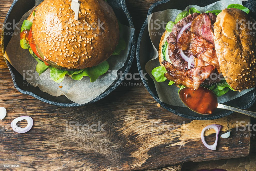 Homemade beef burgers with crispy bacon and vegetables in pans stock photo
