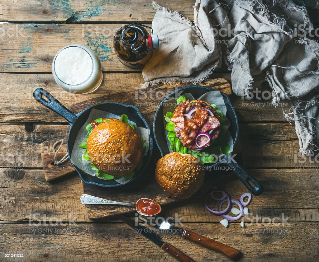Homemade beef burgers with crispy bacon, lettuce and onion rings stock photo
