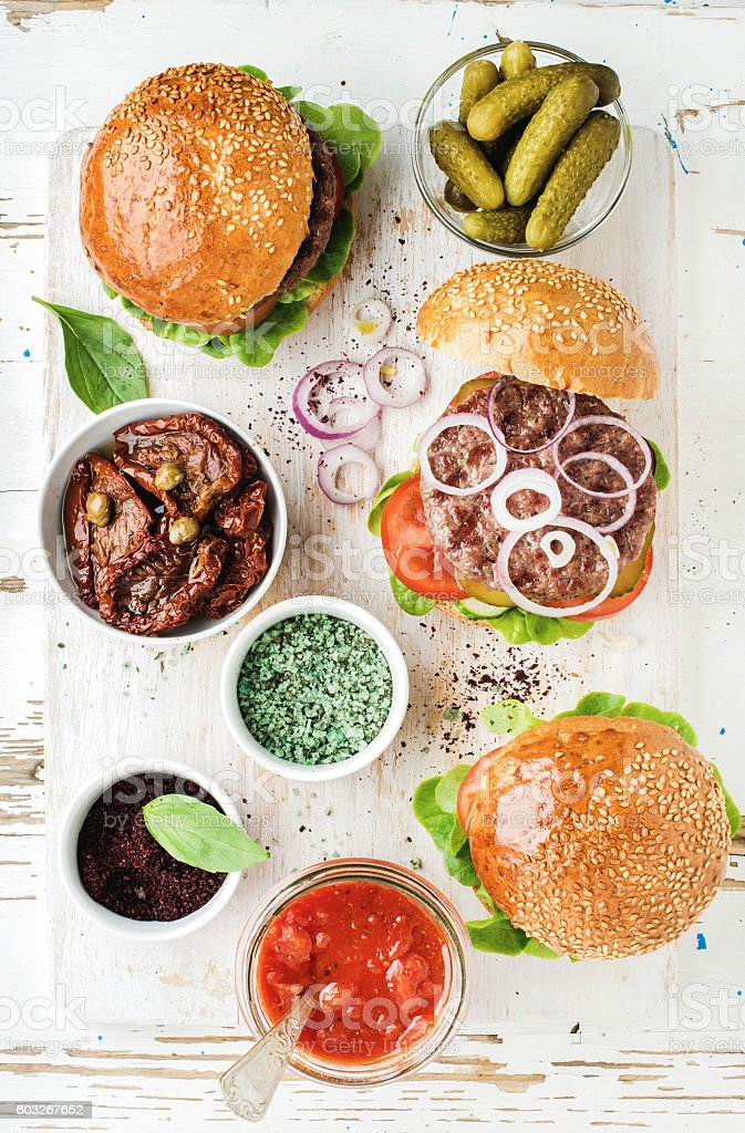 Homemade beef burgers with onion, pickles, vegetables, sun-dried tomatoes stock photo