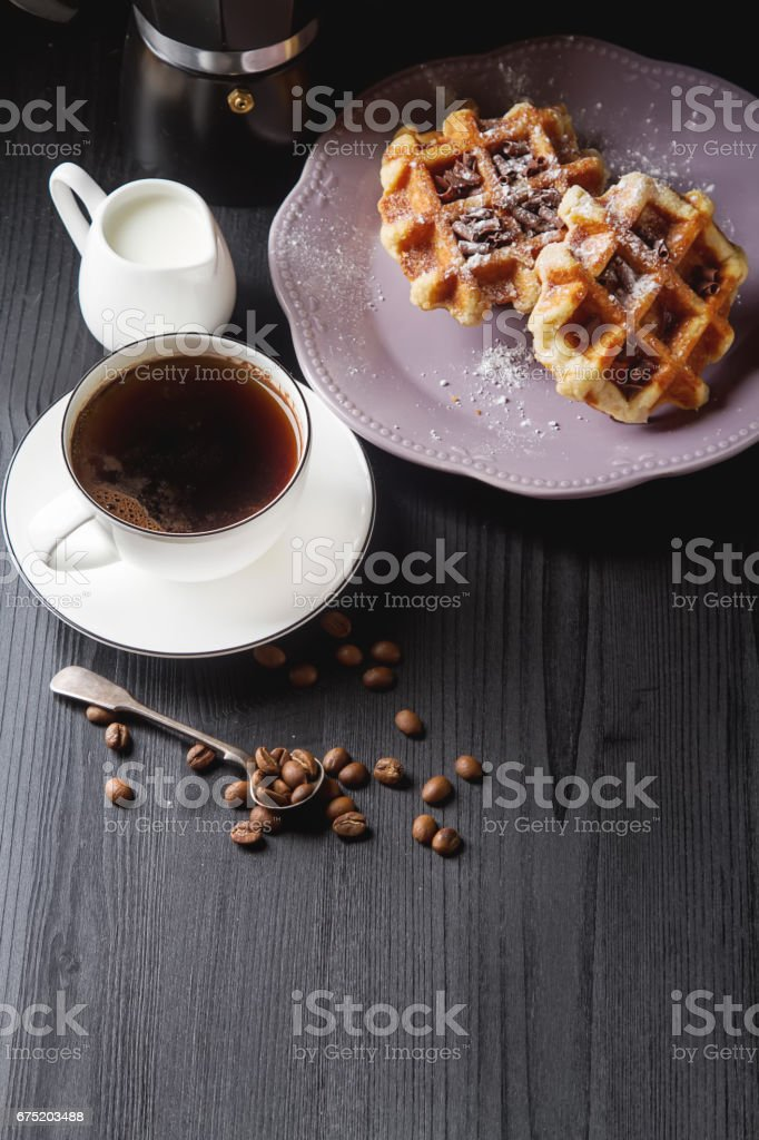 Homemade belgian waffles, white ceramic cup of coffee, milk, teaspoon and coffee beans. Dark rustic background. Space for text in the center. stock photo