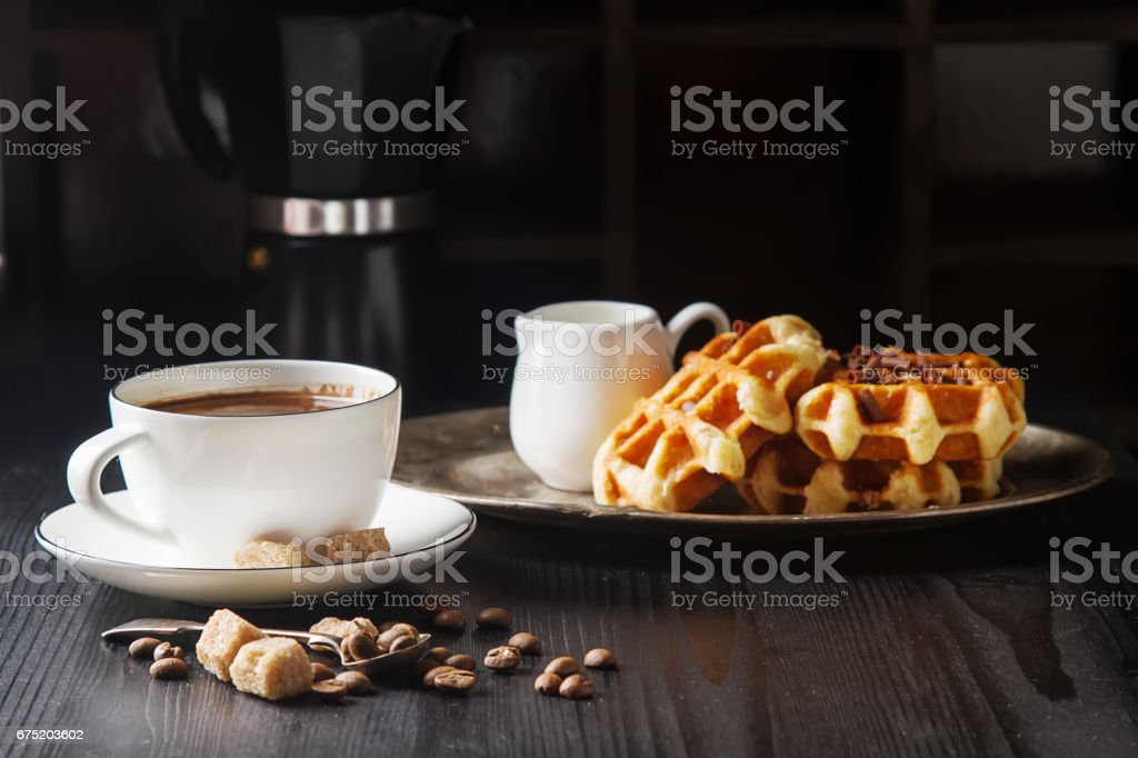 Homemade belgian waffles, white ceramic cup of coffee, milk, teaspoon and coffee beans. Dark rustic background. stock photo