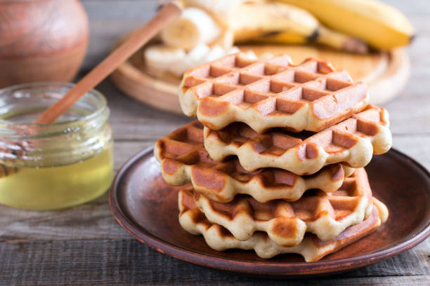 Homemade Belgian waffles with with bananas and honey on a plate Homemade Belgian waffles with with bananas and honey waffle stock pictures, royalty-free photos & images