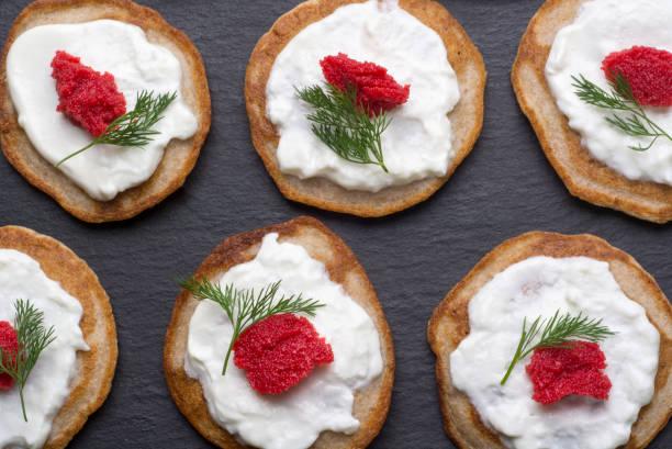 hausgemachte blinis mit sauerrahm und rotem kaviar - buchweizenpfannkuchen stock-fotos und bilder