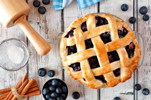 homemade blueberry pie, top view baking scene over a white wood background - blueberry pie stock pictures, royalty-free photos & images