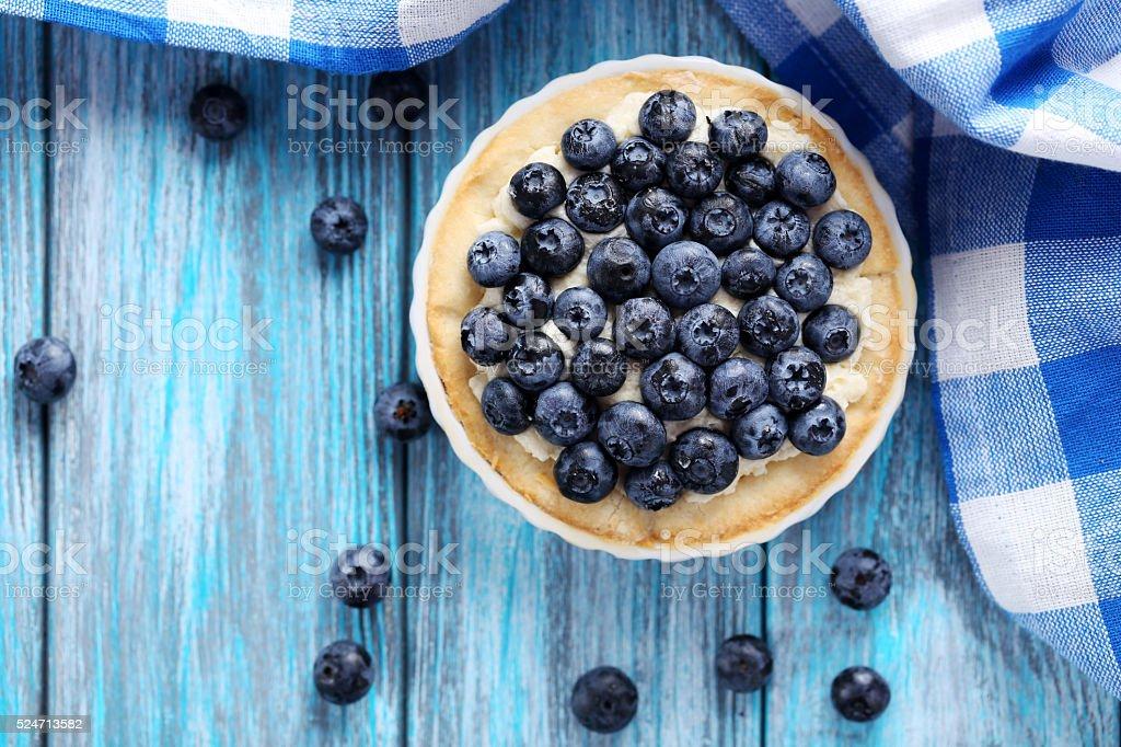 Homemade blueberry tart on blue wooden table stock photo