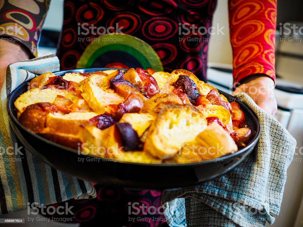 Homemade bread and butter pudding in a woman's hands stock photo
