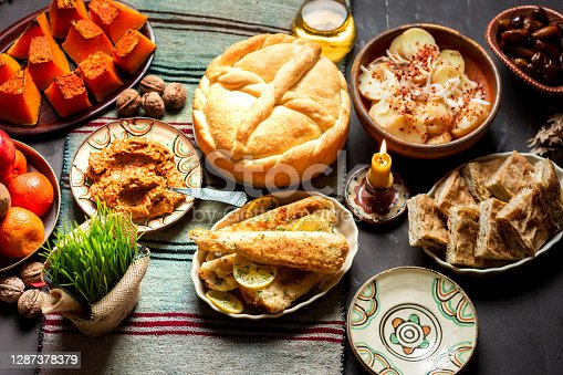 Homemade religiously decorated bread and Orthodox Christmas eve fasting dinner including fish and vegetables on the table. Serbian Christmas Eve celebration and religion abstract