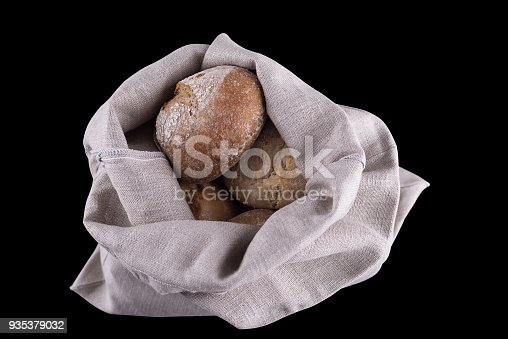 istock Homemade bread in a natural linen bag for storage, isolated on black background 935379032