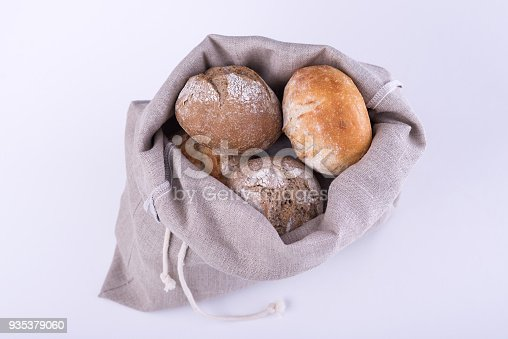 istock Homemade bread in a natural linen bag for storage on white background 935379060