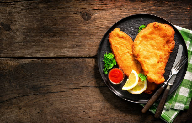 Homemade breaded wiener schnitzel served with parsley and lemon slices stock photo