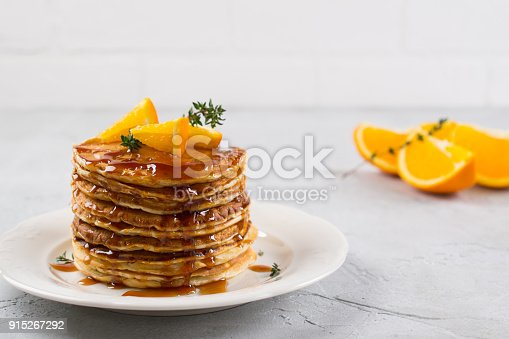istock Homemade breakfast or brunch: american style pancakes served with orange and sprinkled caramel  syrup 915267292