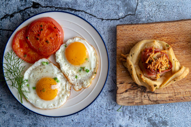 homemade breakfast:bacon puff pastry, fried egg and tomato stock photo