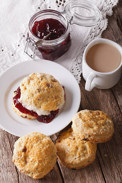 homemade buns with jam and tea with milk close-up. vertical - scone bildbanksfoton och bilder