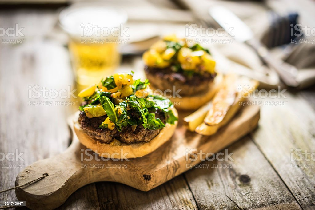 Homemade burgers with fries on wooden background stock photo