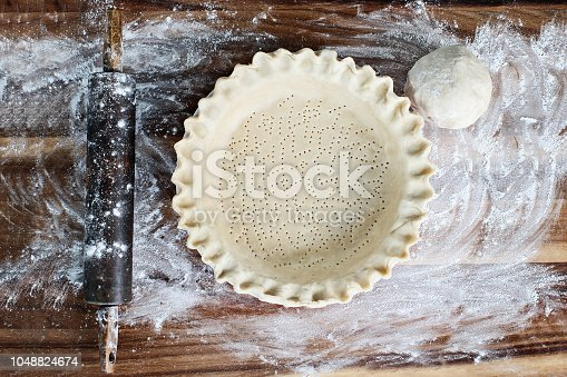 Homemade butter pie crust in pie plate with fluted pinched edge, rolling pin and extra ball of dough over floured rustic wooden background. Crust has been perforated with fork and ready for baking.
