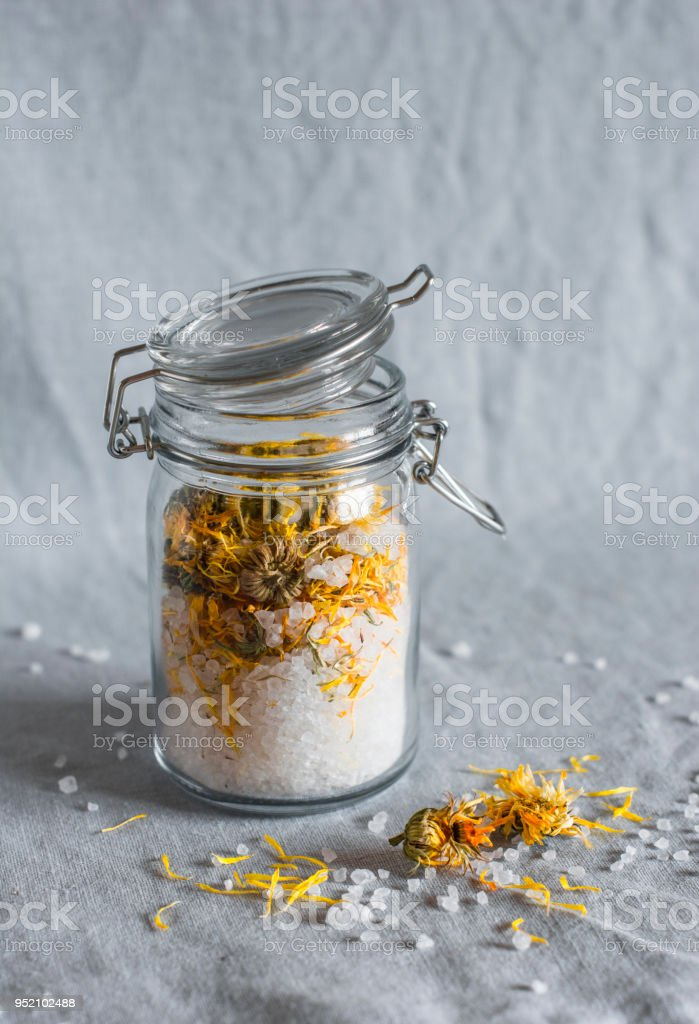 Homemade calendula anti-inflammatory anti-edema sea salt bath on grey background stock photo